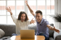 Two people excited as they view their laptop.